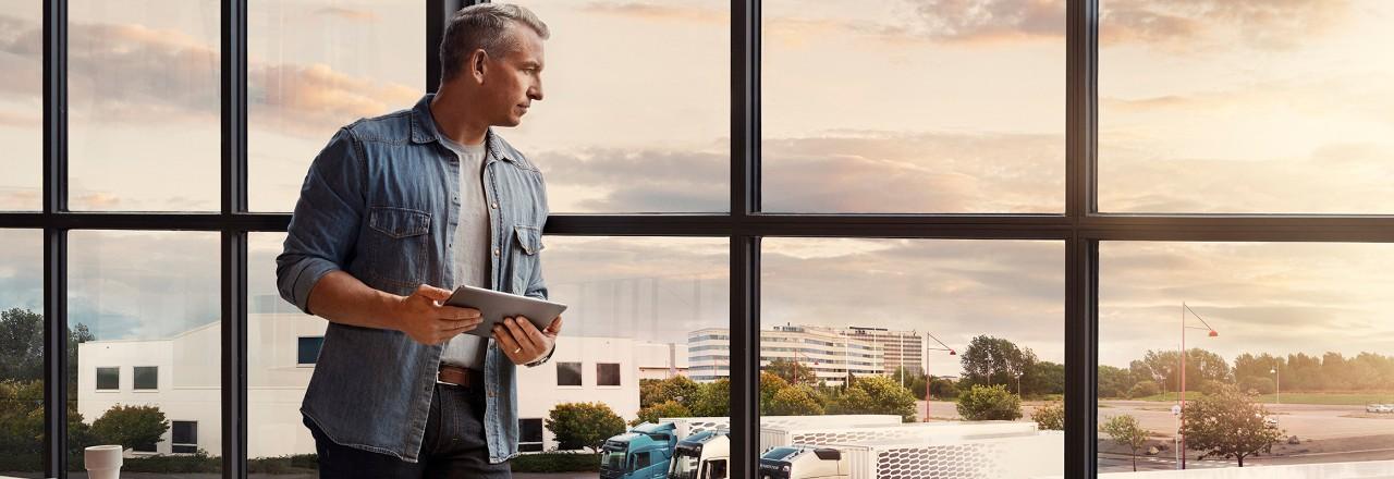 Čovek koji drži tablet stoji pored prozora i gleda u svoj vozni park kamiona